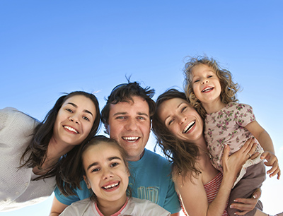 Family smiling blue sky ThinkStockID 159028292 width of 400 pixels